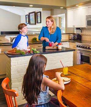 Mamá e hijos están preparando la cena en la cocina.